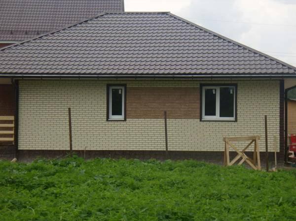 Вид на готовую стену отделки фасада частного дома под кирпич