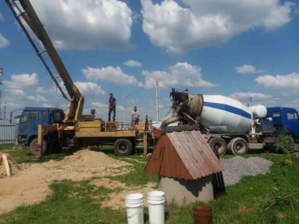Разгрузка готовой смеси в бетононасос для заливки фундамента