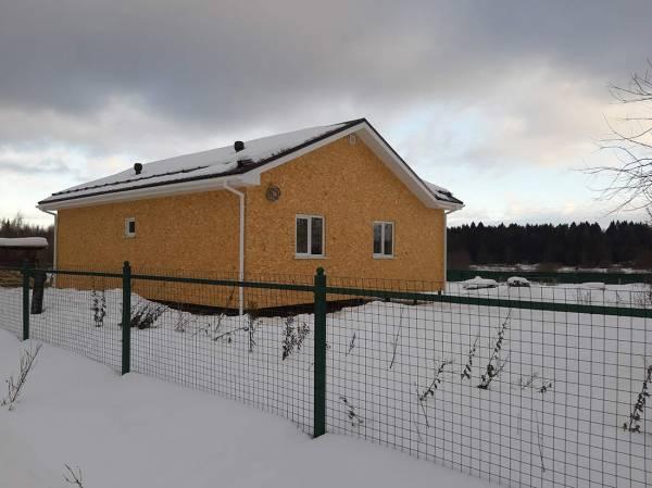 Забор и дом строительство зимой.